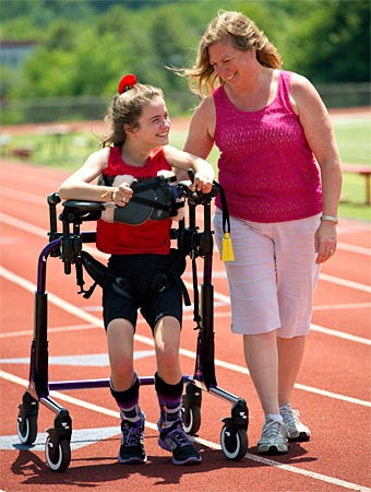 A therapist assists a young girl walking in a gait trainer as she works on motor skills, both smiling at the positive outcomes of the training session at the track